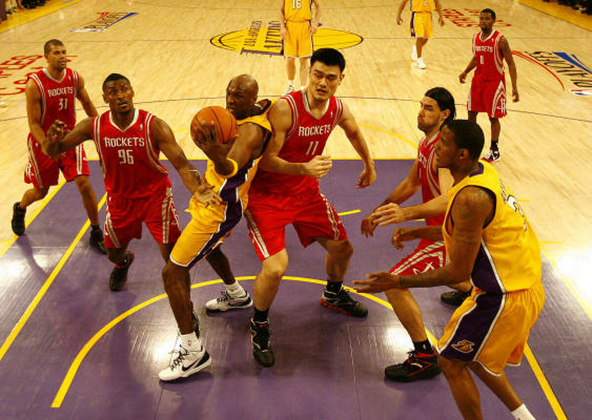 Lakers forward Lamar Odom (7) gets a tough rebound over Rockets defenders Yao Ming, center, Luis Scola, right and Ron Artest in the second quarter.