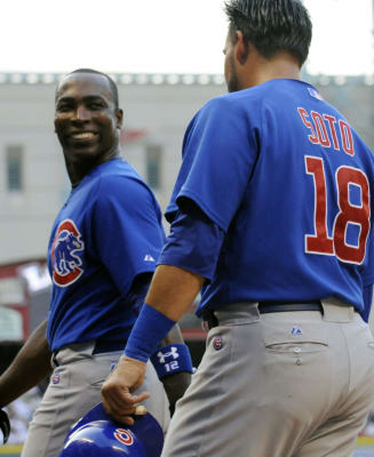 Chicago Cubs' Alfonso Soriano, left, smiles at teammate Geovany Soto as they walk back to the dugout after scoring on a Reed Johnson three-run triple in the first inning.