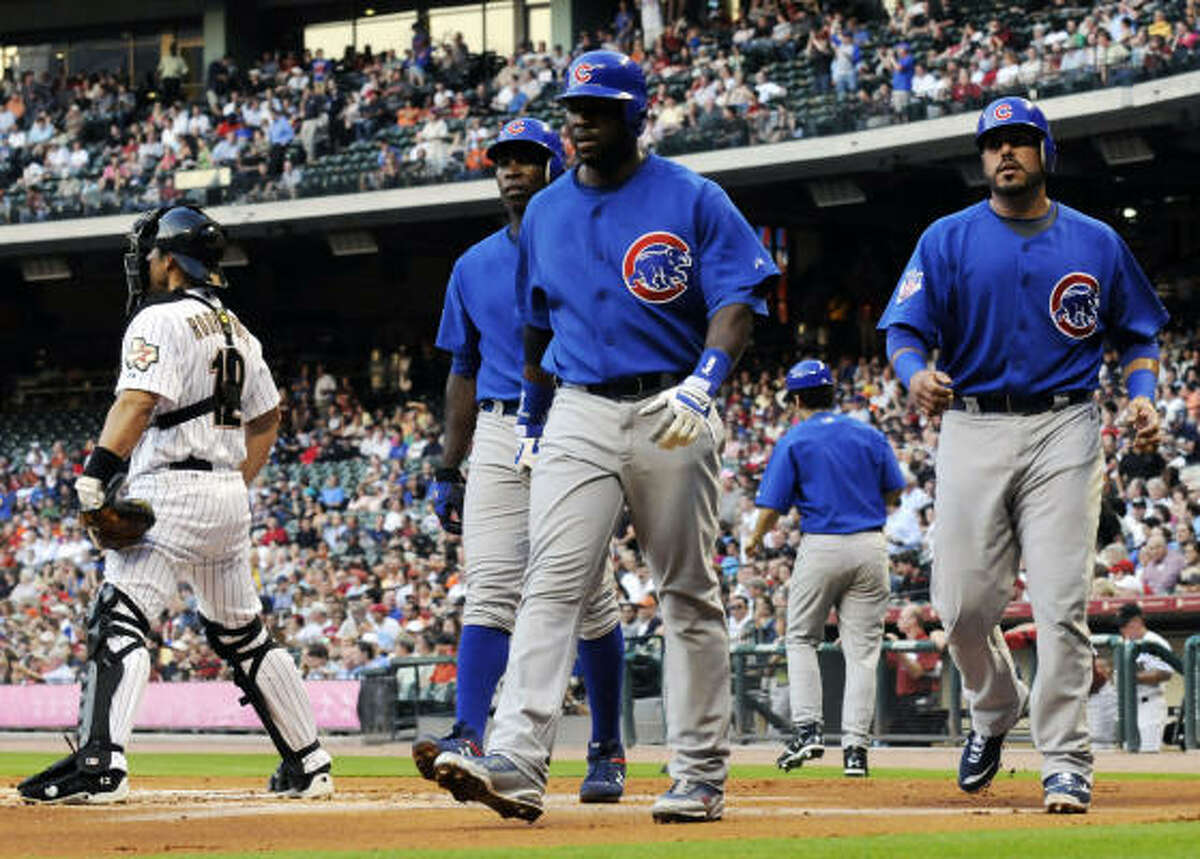 Chicago Cubs' Milton Bradley, center, leads teammates Alfonso Soriano, behind, and Geovany Soto, right, to the dugout after the three scored on a Reed Johnson triple to deep center field in the first inning.