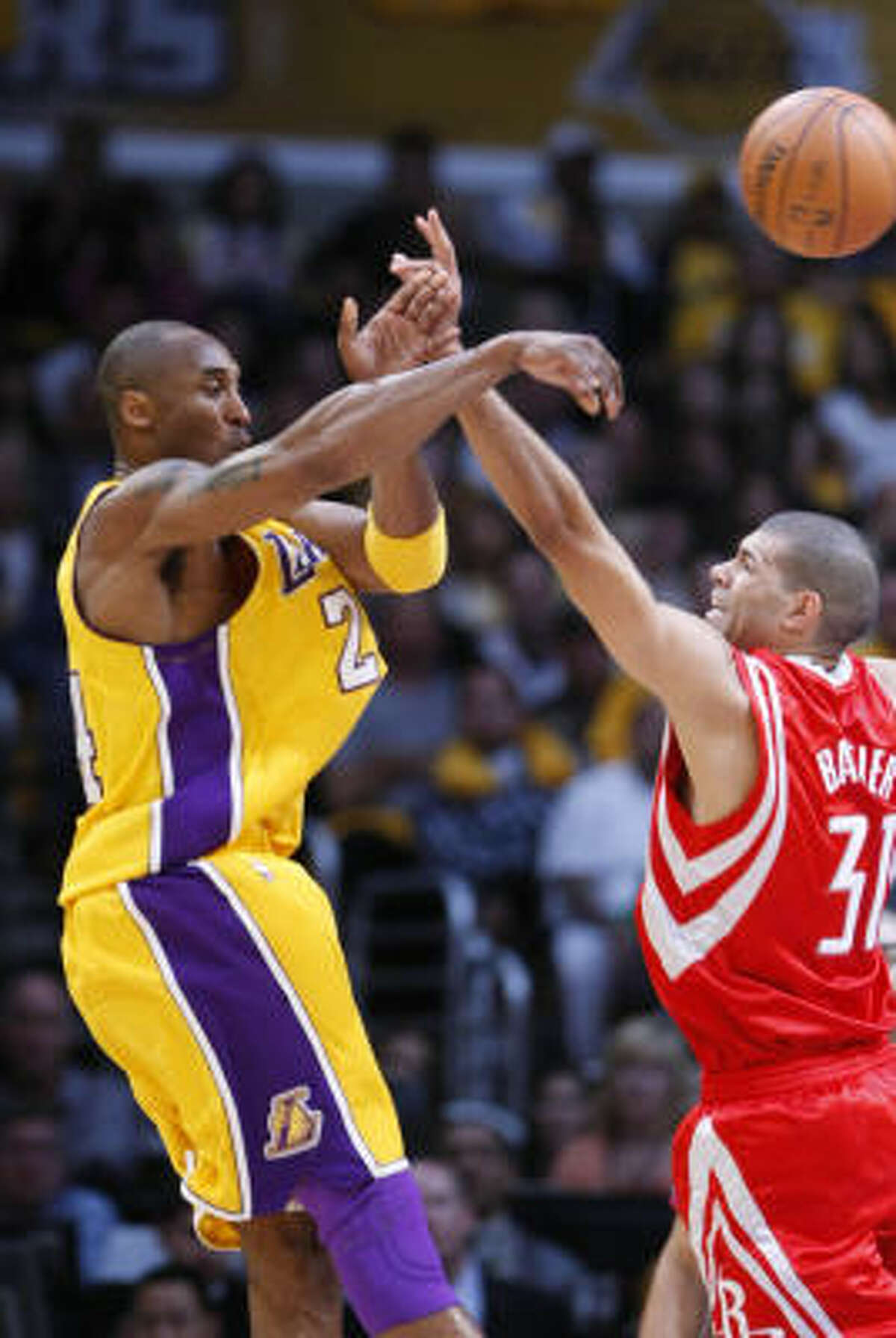 Lakers guard Kobe Bryant, left, has to dish the ball as forward Shane Battier defends in the first quarter.