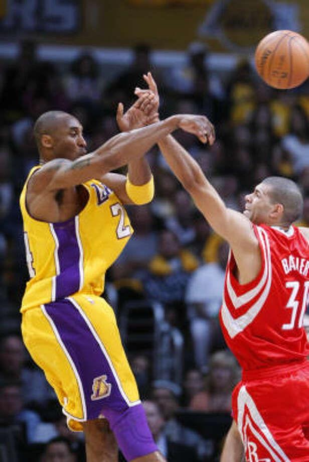 Lakers guard Kobe Bryant, left, has to dish the ball as forward Shane Battier defends in the first quarter. Photo: Nick De La Torre, Chronicle