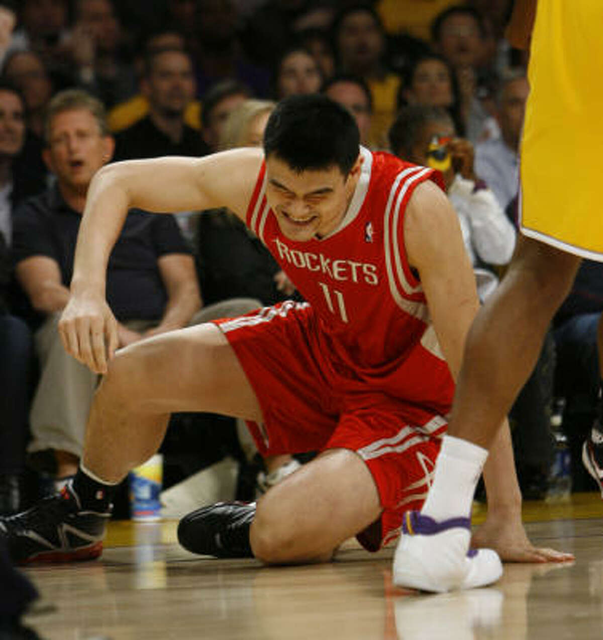 Rockets center Yao Ming (11) winces after being knocked down by the Lakers in the first quarter of Game 1 at Staples Center in Los Angeles. It wasn't the first time Yao had to get up after being knocked down.