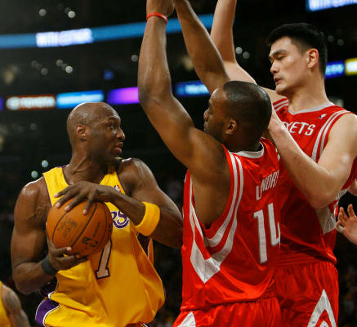 Lakers forward Lamar Odom (left) had trouble scoring against Rockets forward Carl Landry (14) and center Yao Ming in the third quarter of Game 1.
