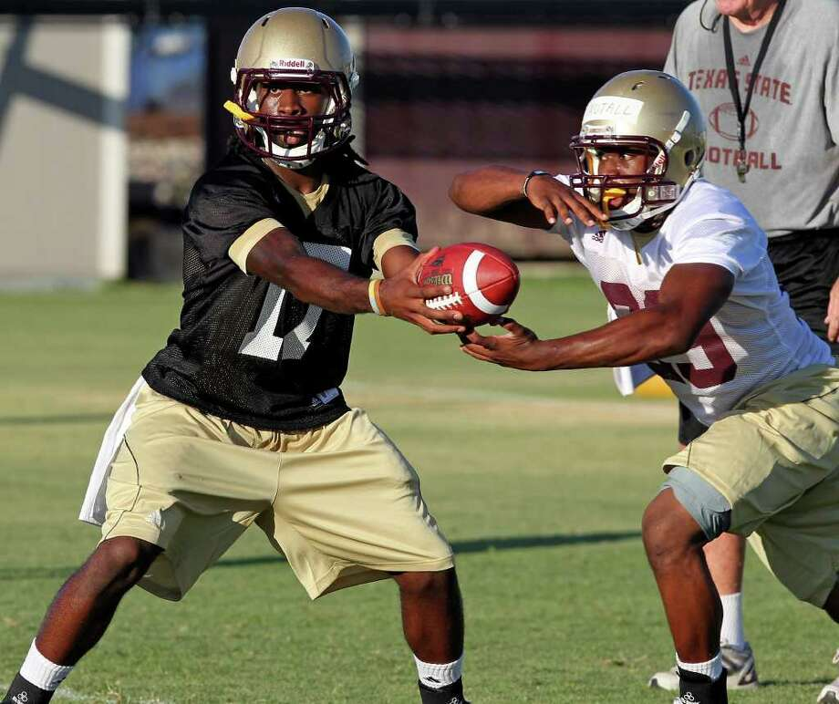 Quarterback Shaun Rutherford (left) hands off during Texas State's first practice with new head coach Dennis Franchione on Friday, Aug. 5, 2011. Photo: Tom Reel/treel@express-news.net / © 2011 San Antonio Express-News