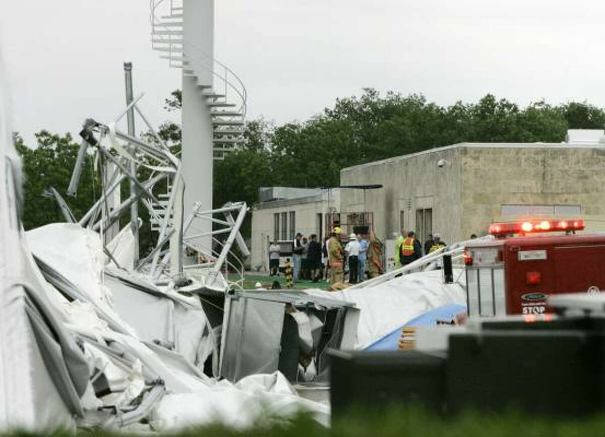 Emergency personnel work around the remains of the Cowboys' practice field structure in Irving.