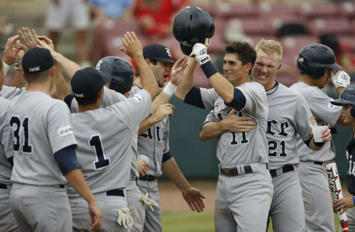 Rice's Rick Hague (11) celebrates with teammates after Hague's home run broke a 3-3 tie in the Owls' win.