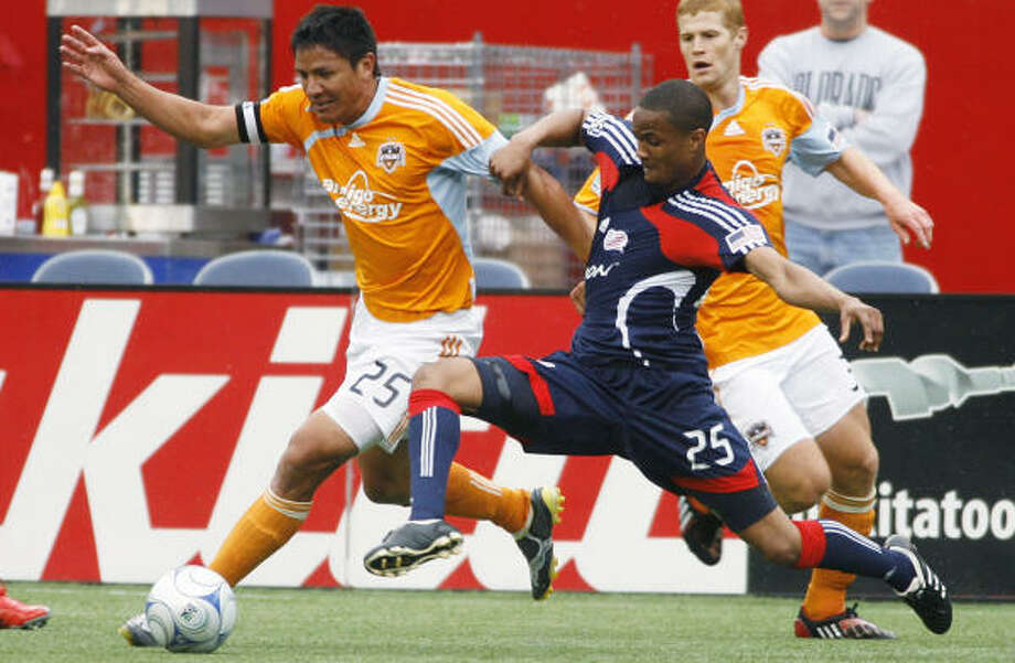 Dynamo forward Brian Ching, left, battles for the ball with Revolution defender Darrius Barnes during the second half. Photo: Stew Milne, AP