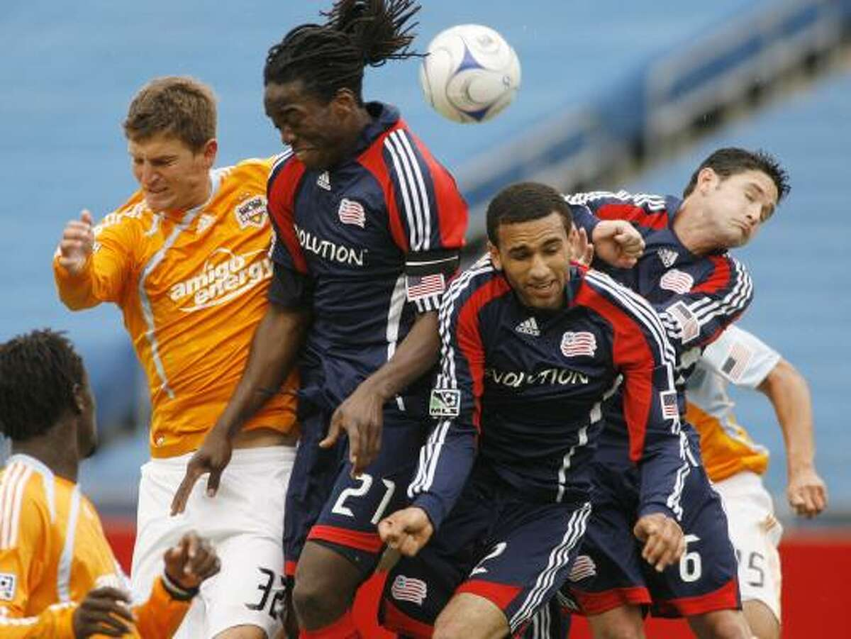 Dynamo defender Bobby Boswell, left, battles for the ball after a corner kick against Revolution midfielder Shalrie Joseph (21) and defenders Amaechi Igwe (2) and Jay Heaps (6) during the second half.