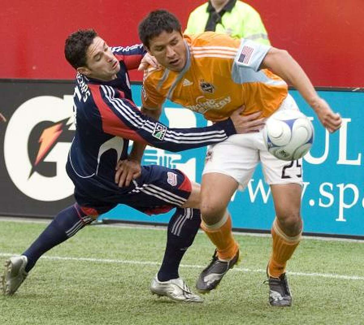 Dynamo forward Brian Ching, right, tries to break away from Revolution defender Jay Heaps during the first half.