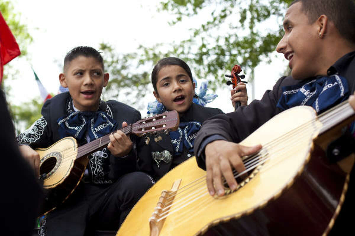 Members of the International Mariachi Mecca, 11-year-old Jovani Campos, 8-year-old Beatriz Lozano and Jesus Sanchez warm up prior to the LULAC 17th Annual Cinco de Mayo parade in downtown Houston, Texas.