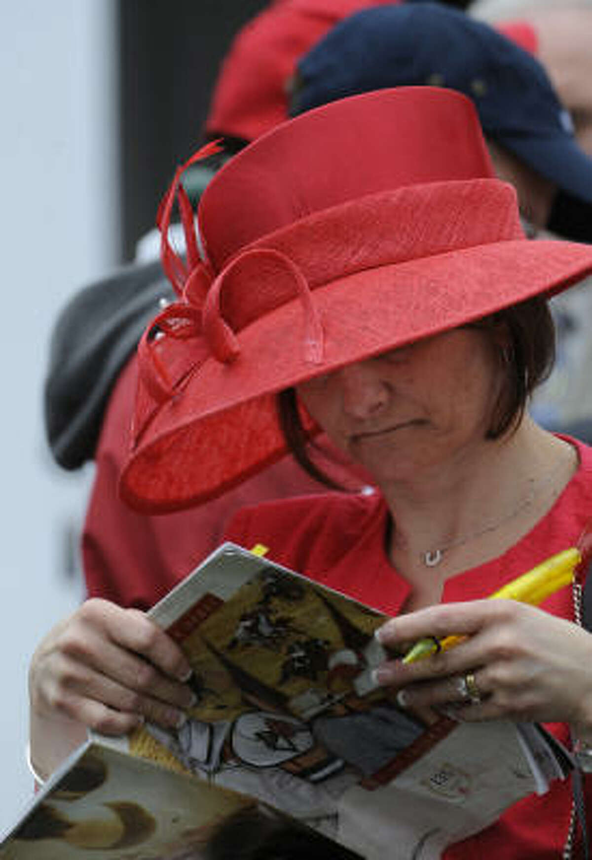 A derby patron flips through a race program, sporting one of the unique hats for which the Run for the Roses is famous.