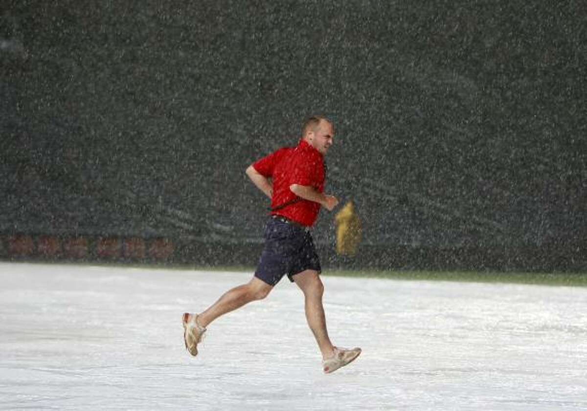 A Turner Field grounds crew member run across the infield tarp as heavy rain stops the game in the eighth inning.