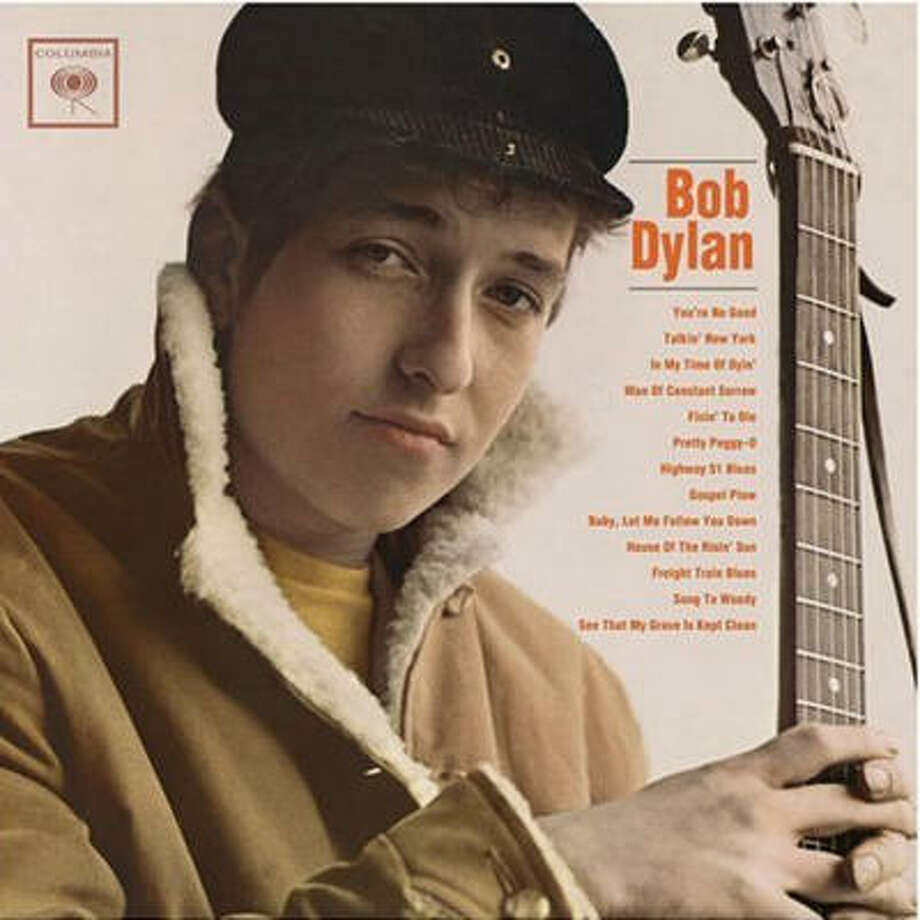 Bob Dylan(1962): He was introduced earnestly, a round-faced folkie with the fisherman's cap and wool-collared winter coat looking straight ahead. He seems bemused by the attention, struggling to stifle a smile.