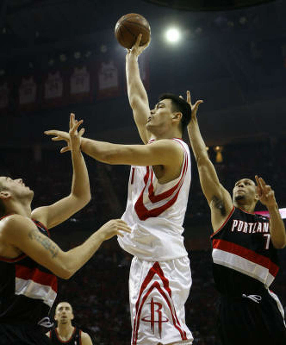 Rockets center Yao Ming (center) shoots over Portland Trail Blazers guard Brandon Roy (7) and center Joel Przybilla during the first quarter of Game 6 of their first-round series at Toyota Center.