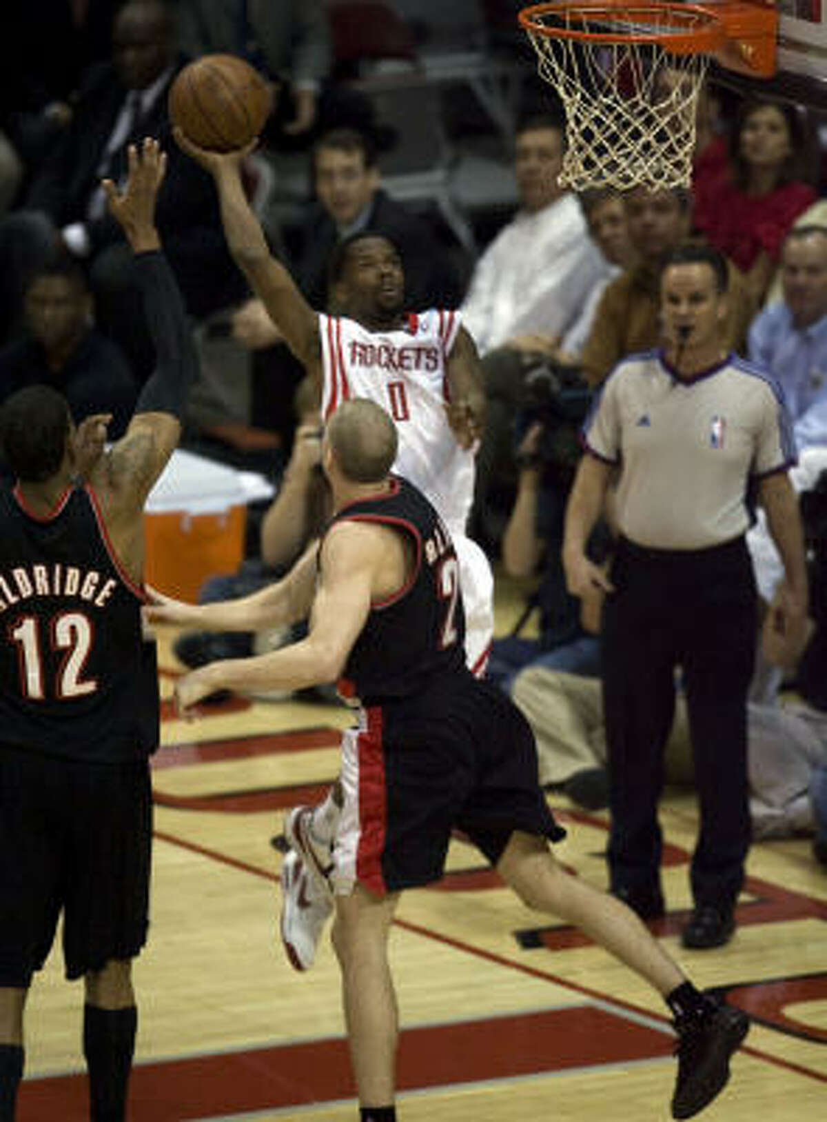 Rockets guard Aaron Brooks (0) takes a shot over Portland Trail Blazers guard Steve Blake (2) and forward LaMarcus Aldridge (12) during the first quarter.