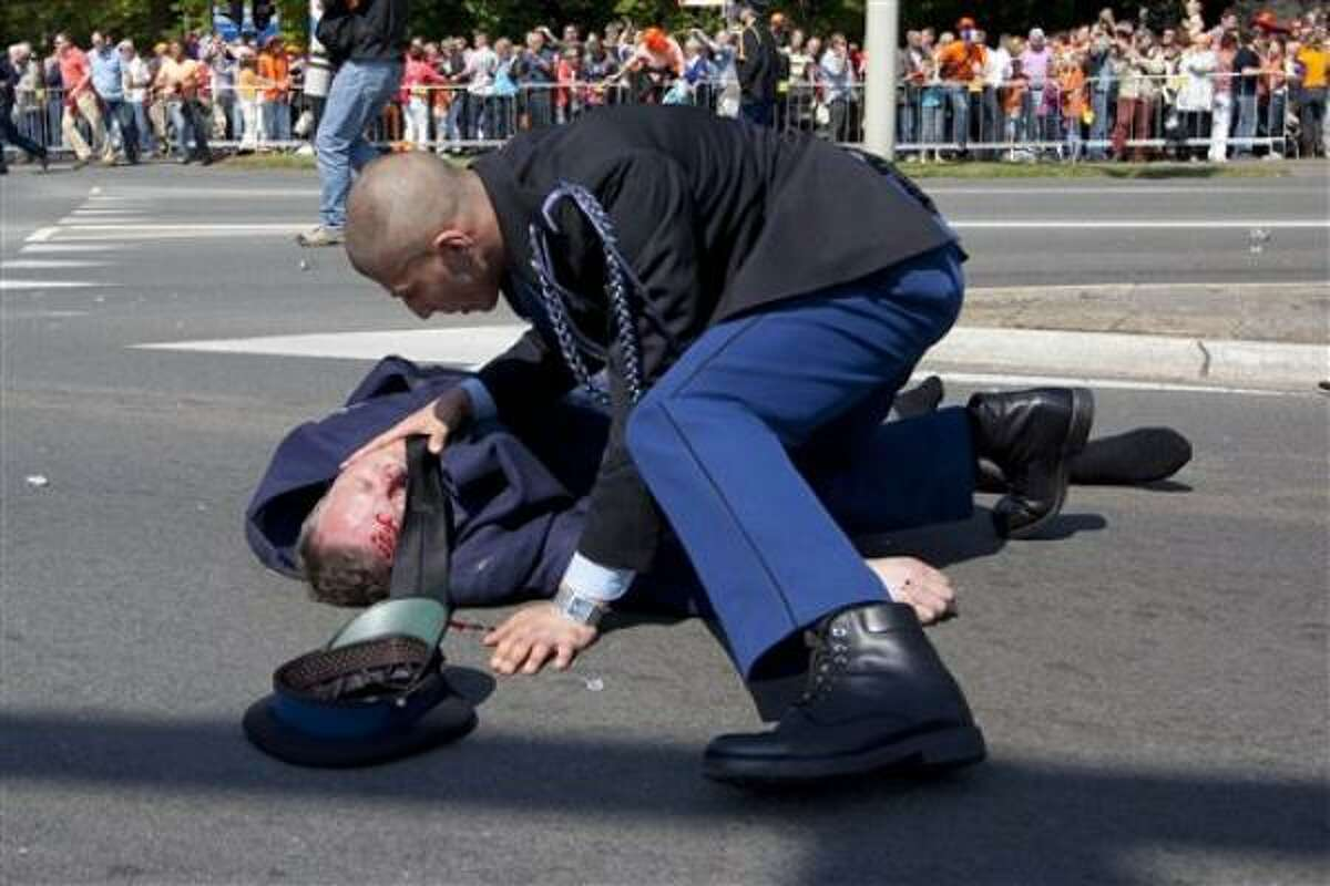 A police officer attemps to aid an injured person.