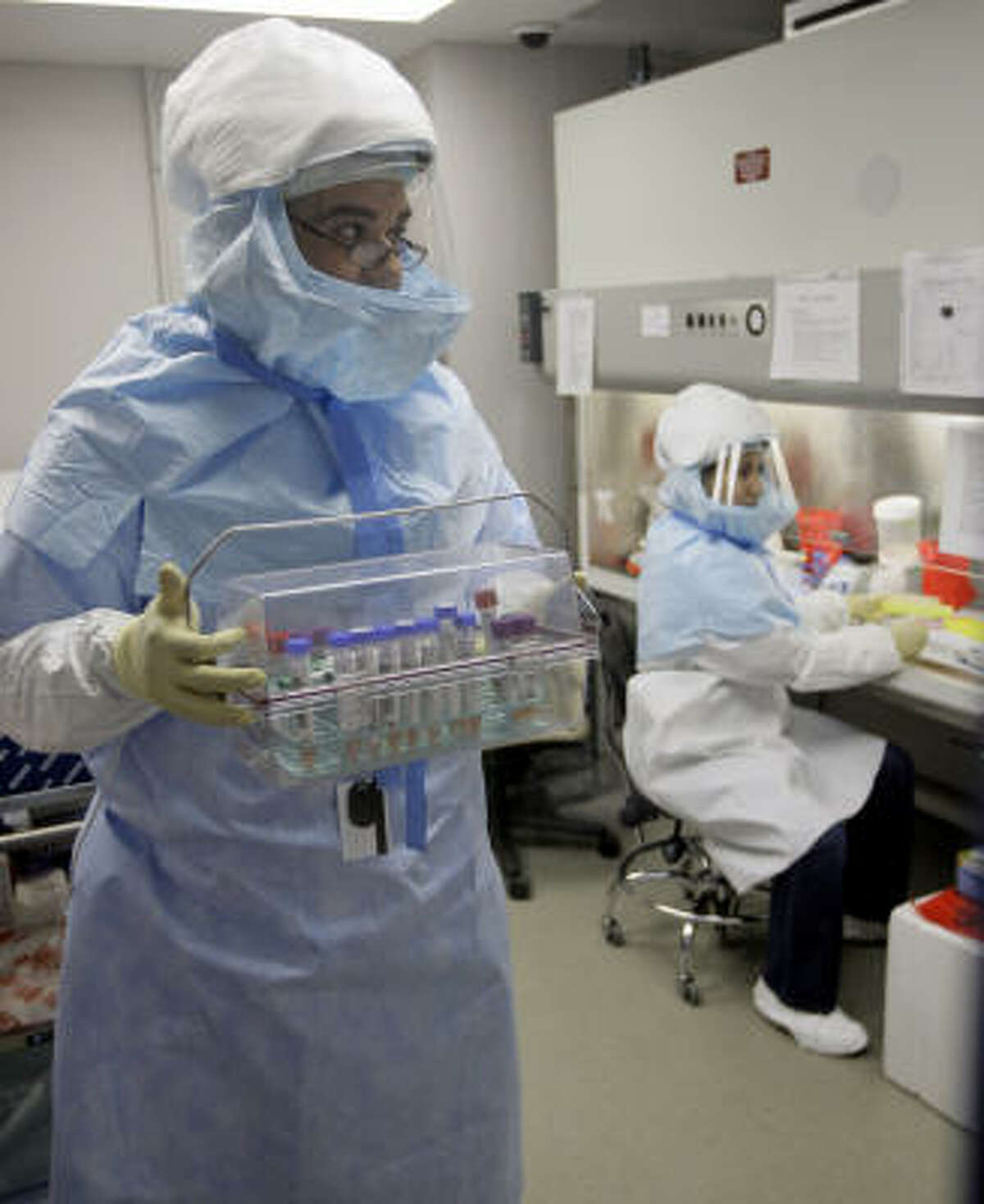 Microbiologist Gilbert Ortiz, left, handles samples while testing for swine flu along with lead scientist Lupe Garbalena, right, at the Houston Department of Health and Human Services.