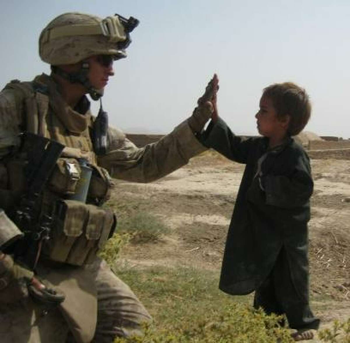 My son, Sgt. William W. Rollins, while deployed in Afghanistan. He said the little guy had a lot to say but he didn't understand a word, but was glad he was there to listen and making a better place to live for these children. - Barbara Rollins For more information on the KSBJ