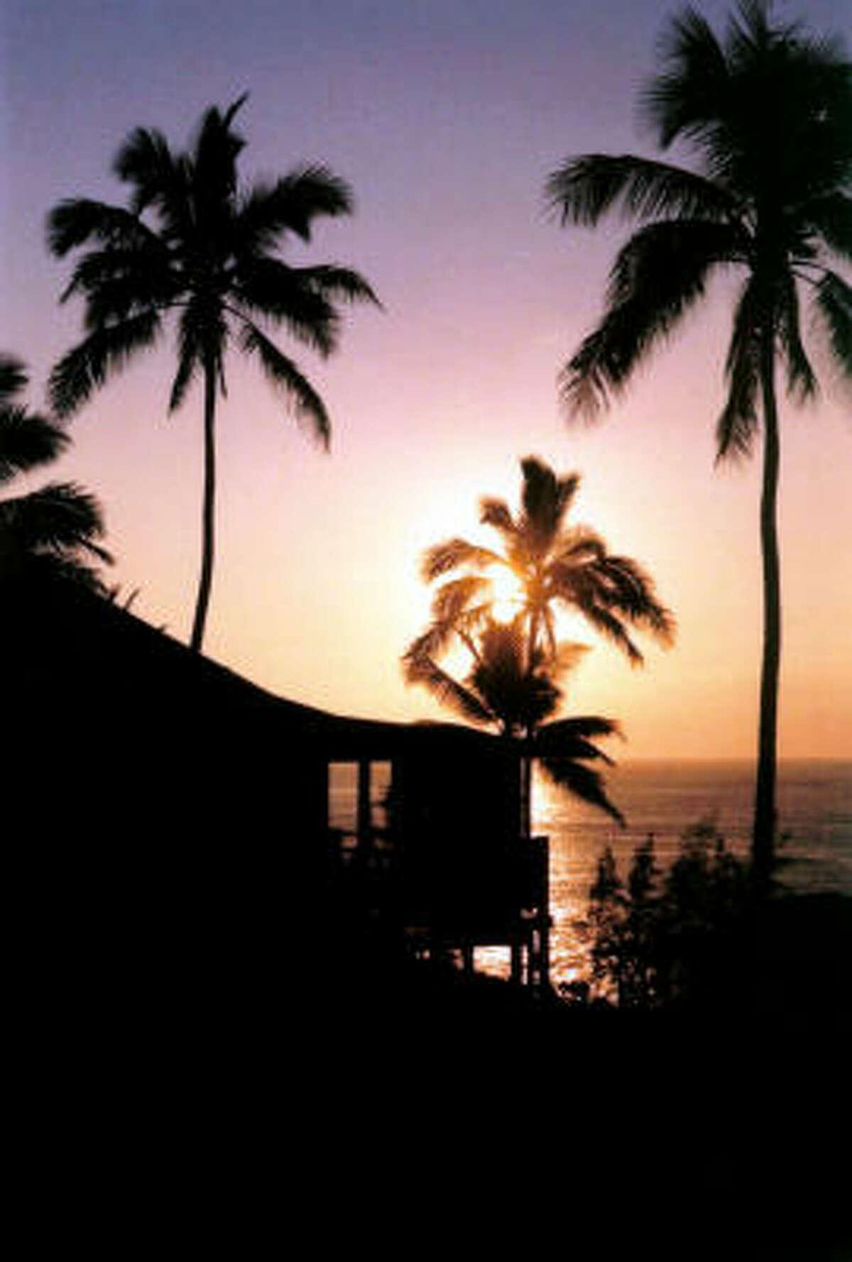 The sun sets beyond a Hotel Hana-Maui Sea Ranch Cottage.