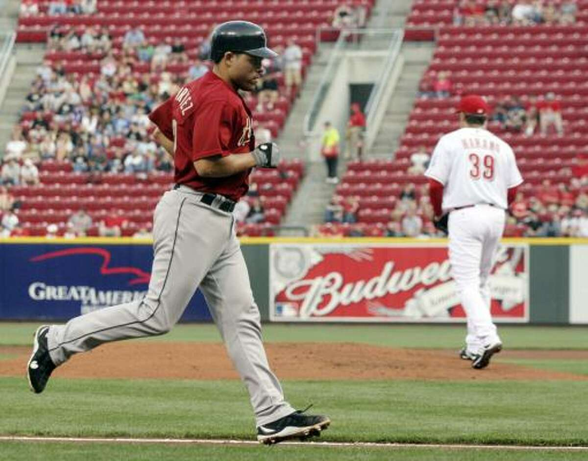 Astros catcher Ivan Rodriguez heads for home plate after hitting a home run off Cincinnati Reds pitcher Aaron Harang, right, in the second inning.