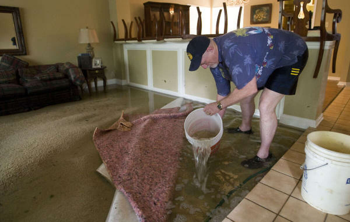 Burton Barnes bails water at his brother-in-law's house at Bear Creek.
