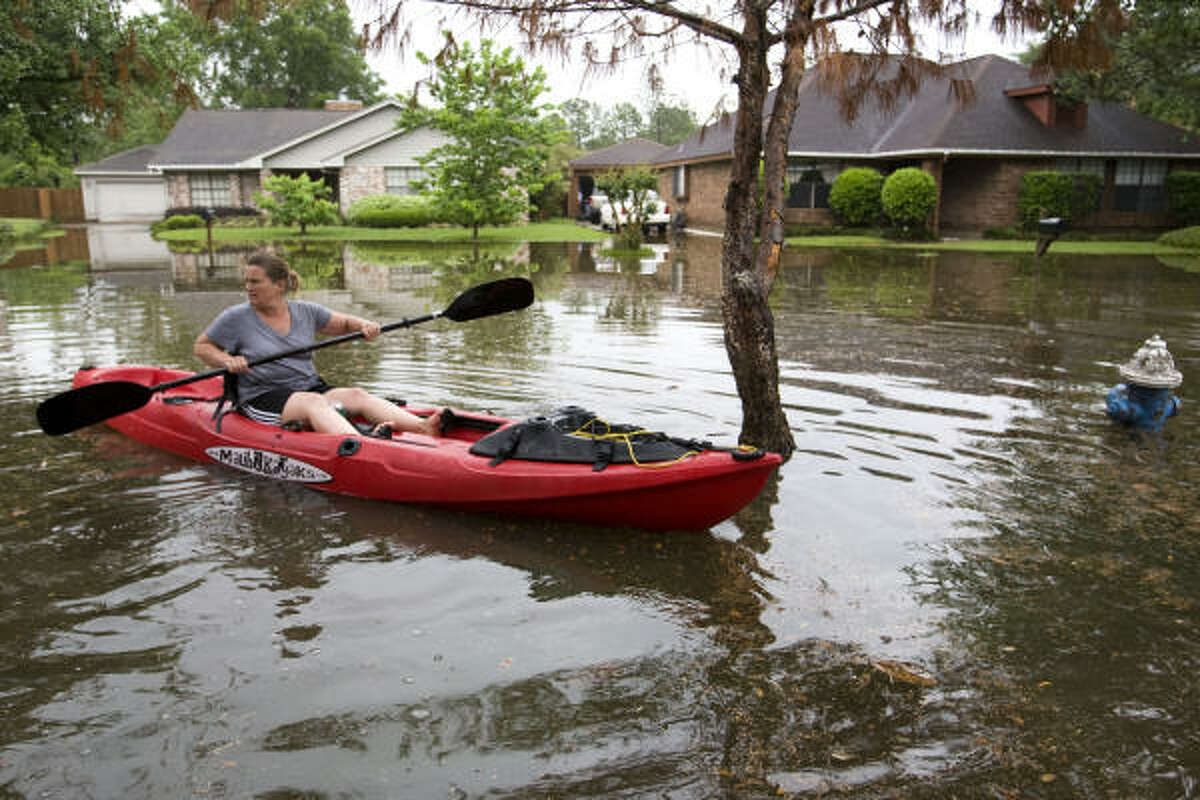 Kelly Campbell paddles at Bear Creek. Heavy rains overnight in the area flooded several streets and homes in the subdivision.