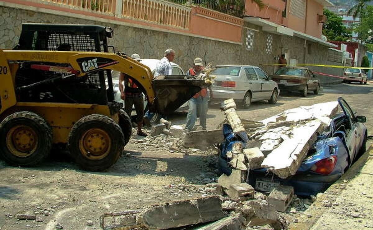 Workers try to remove the debris from a car in Acapulco, Guerrero state. The quake happened about 80 miles from Acapulco.