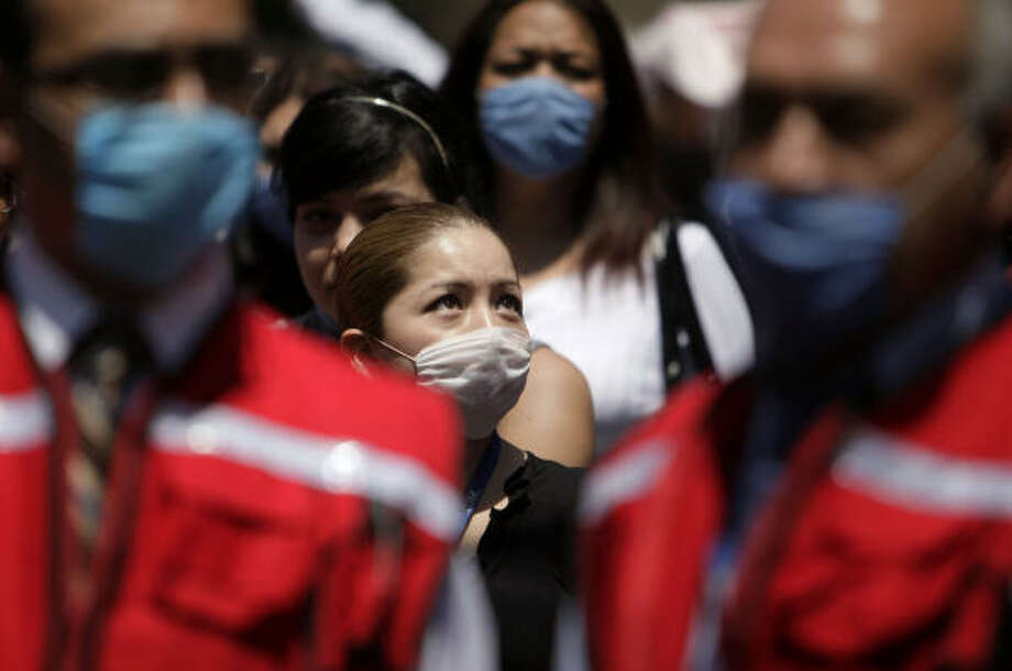 People are evacuated from their buildings wearing surgical masks after the earthquake. Photo: Gregory Bull, Associated Press