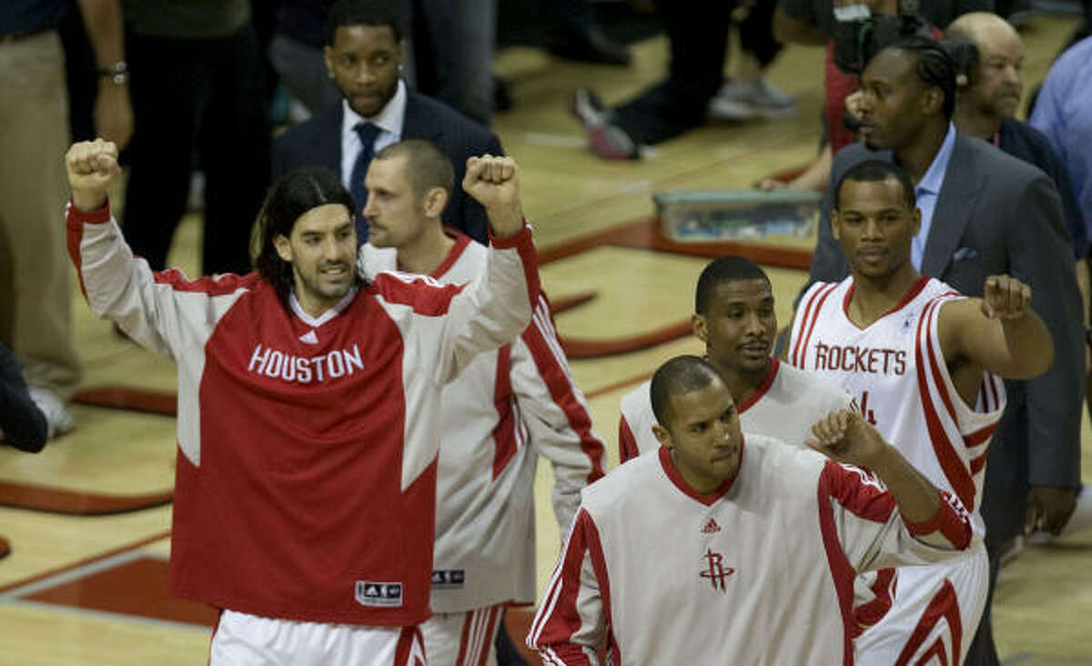 Rockets forward Luis Scola (left) celebrates with teammates after defeating the Portland Trailblazers.