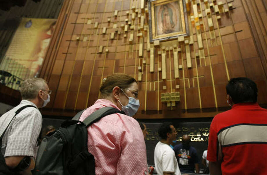 People are seen wearing protective masks as they pay respects to Our Lady of Guadalupe. Photo: Julio Cortez, Chronicle