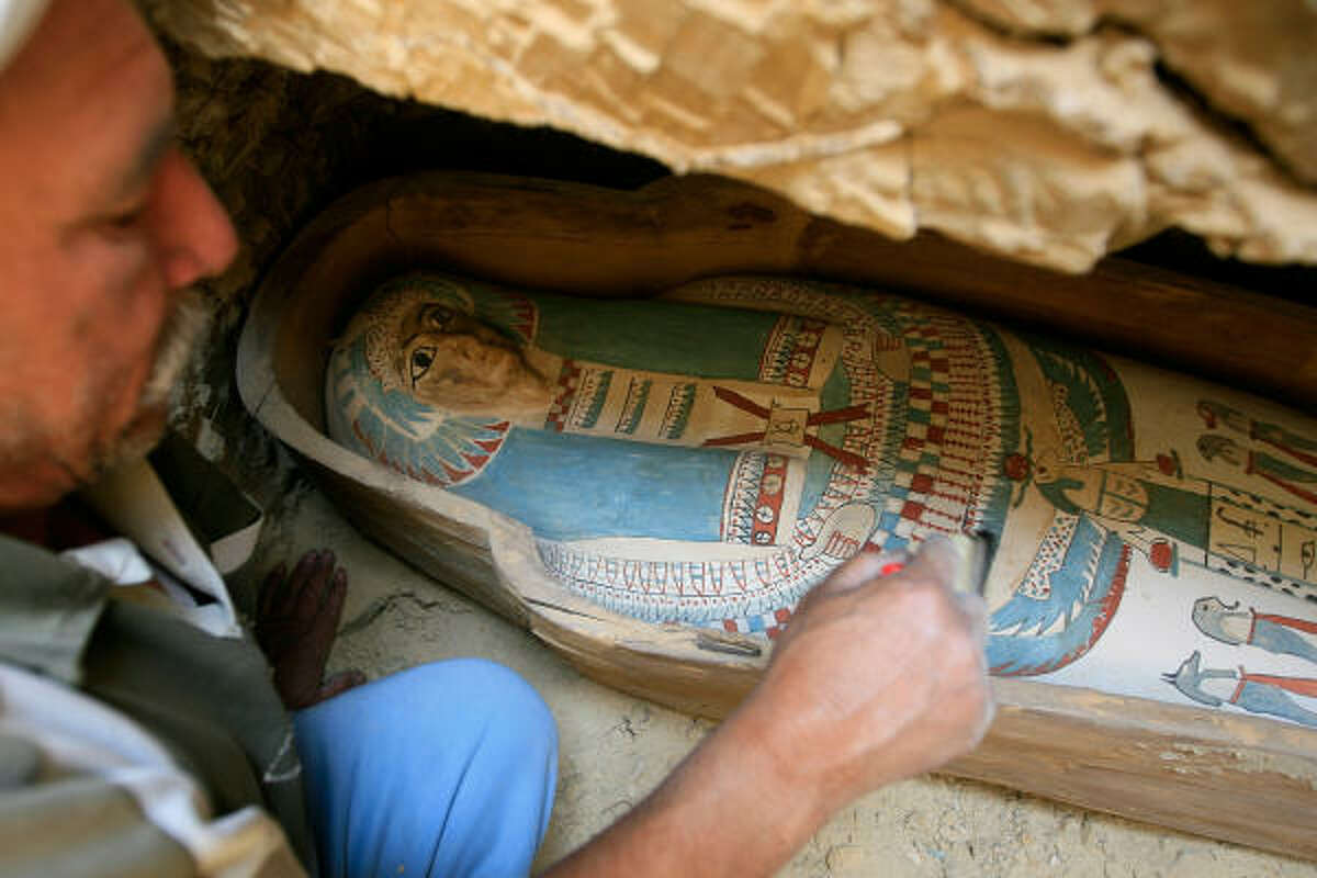 An Egyptian worker brushes the dust off a wooden coffin containing a linen-wrapped mummy found in a necropolis southeast of the pyramid field of Lahun.