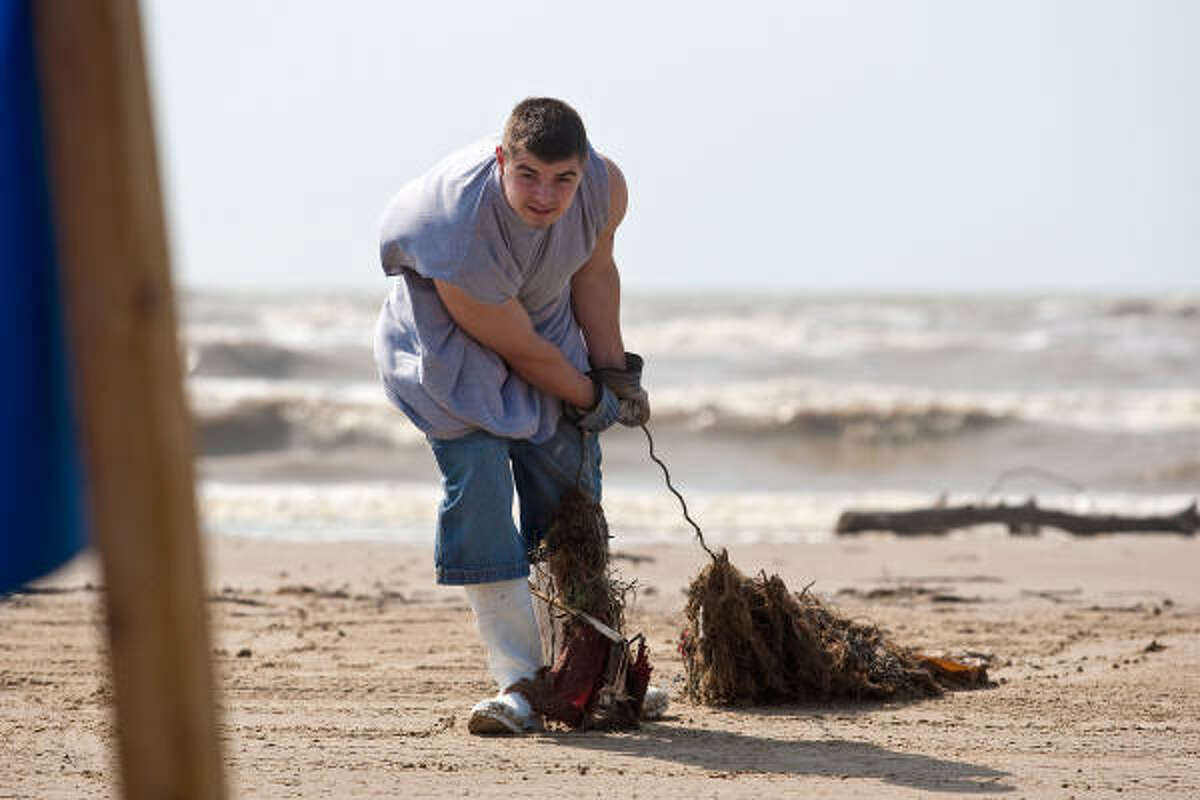 Michael Scapuzzo drags a net filled with debris away from the beach during a massive cleanup effort,on Crystal Beach on the Bolivar Peninsula.