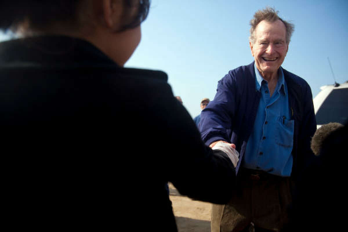 Former President, George H. W. Bush shakes hands with a Crenshaw Elementary School student volunteer, during a massive cleanup effort, on Crystal Beach on the Bolivar Peninsula.