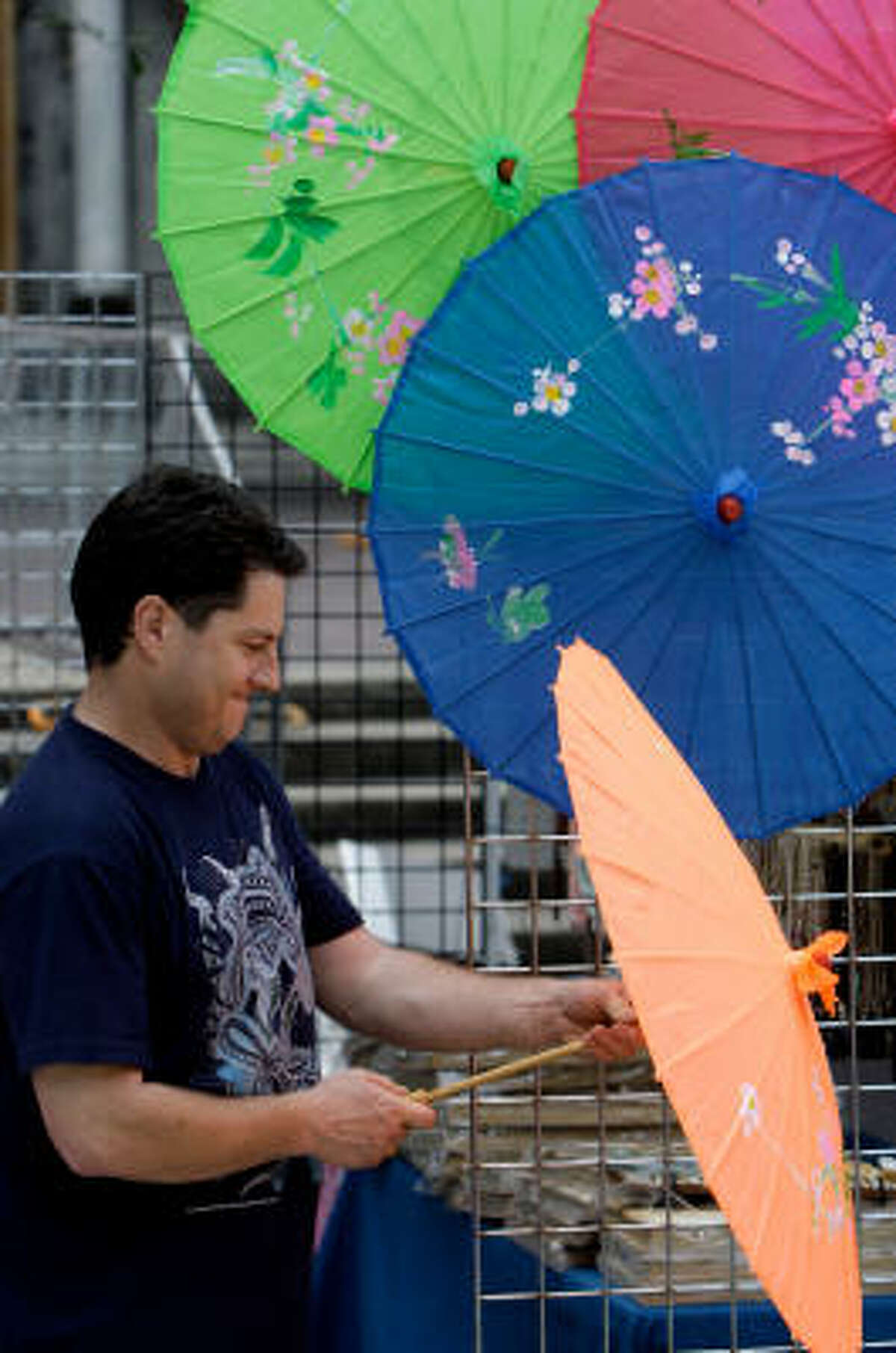 George Bass of San Antonio displays hand-painted bamboo umbrellas at his booth named World of Wonders at iFest the Houston International Festival held downtown in Houston.