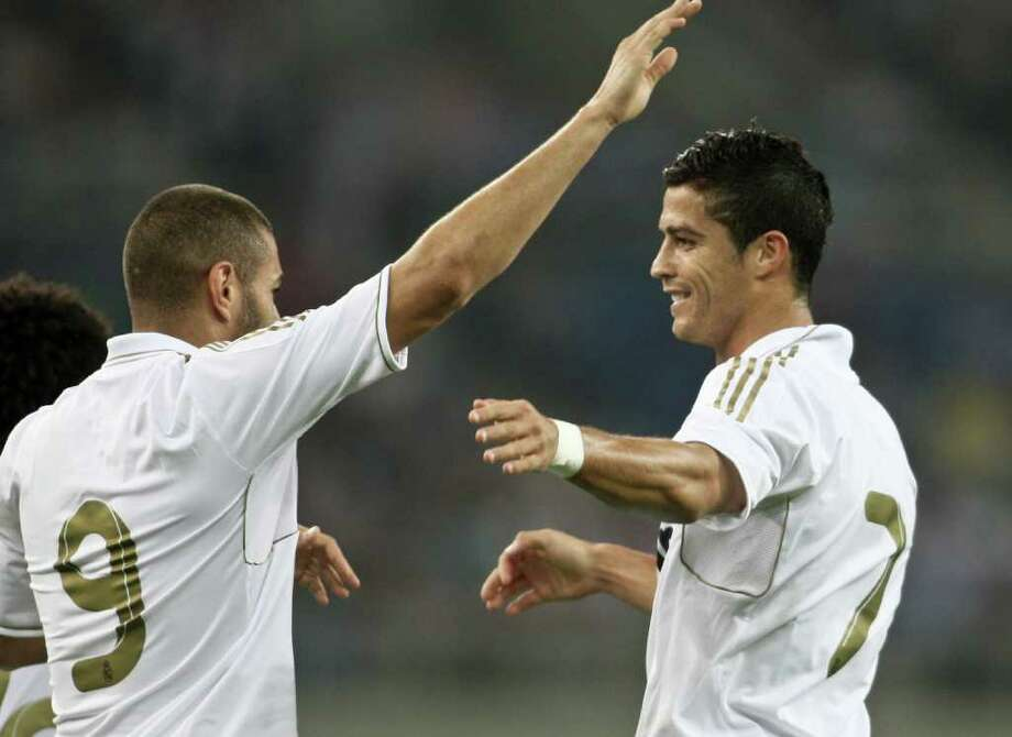 Real Madrid's Cristiano Ronaldo, right, celebrates with his teammate Karim Benzema after they scored a goal against Tianjin Teda during a friendly match in Tianjin, China on Saturday, Aug. 6, 2011. Real Madrid defeated Tianjin Teda 6-0 in their China tour. (AP Photo) CHINA OUT / COLOR CHINA PHOTO