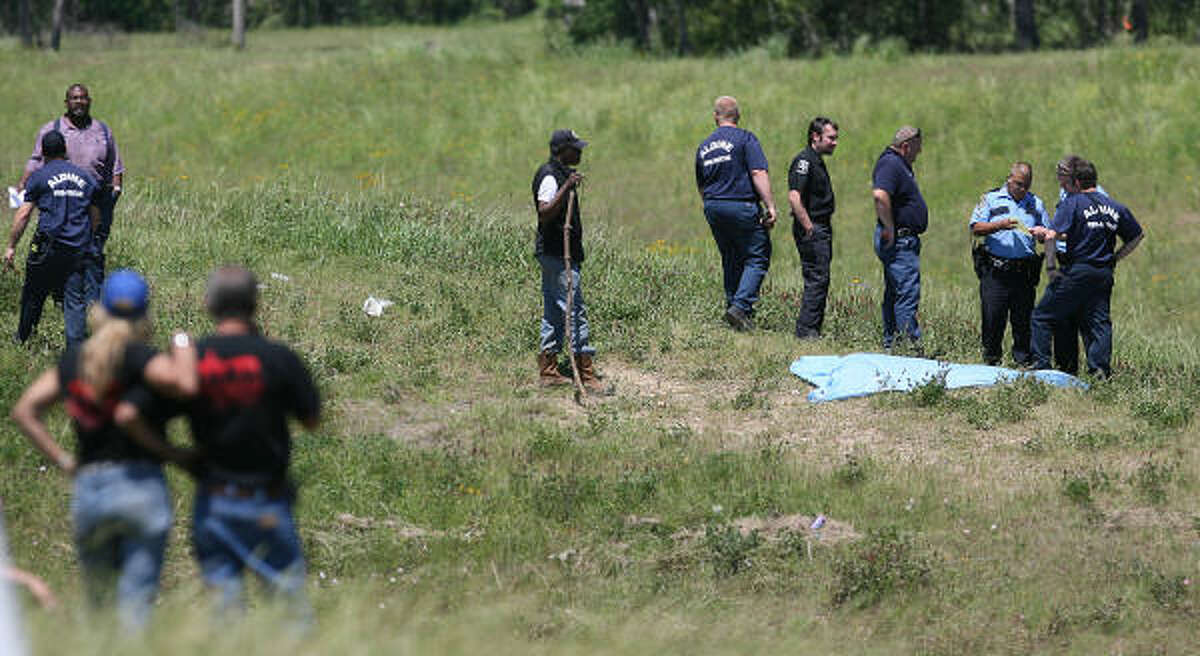 Police and investigators along Greens Bayou surround the remains of Hallie Jenkins, 4, found on April 21, three days after the crash.