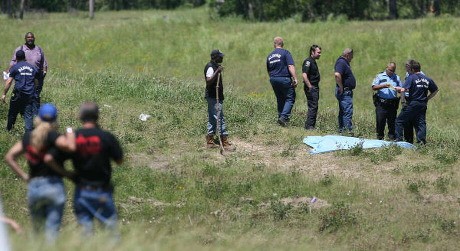 Police and investigators along Greens Bayou surround the remains of Hallie Jenkins, 4, found on April 21, three days after the crash. Photo: Mayra Beltran, Chronicle