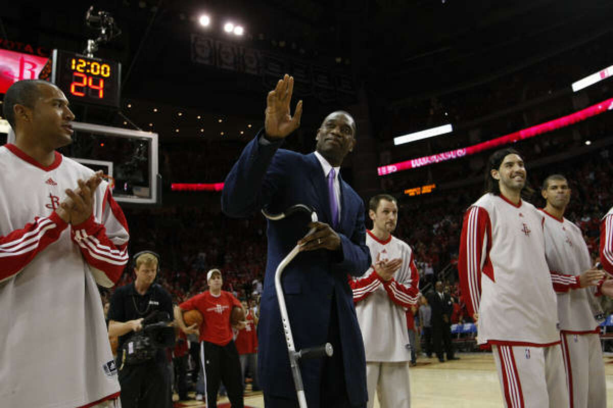 Rockets center Dikembe Mutombo, center, waves to the crowd before the start of Game 3. Mutombo was honored before the game by a national organization of basketball writers for his charity work.