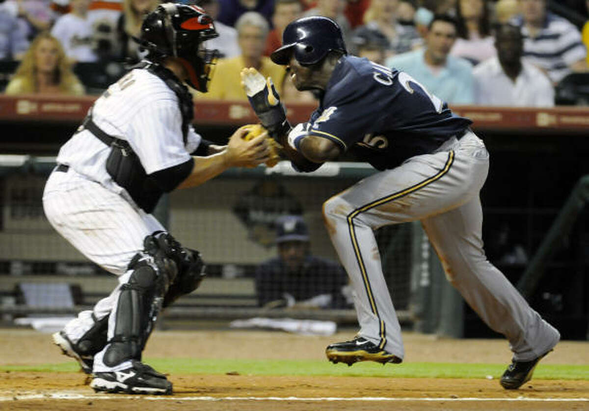 Milwaukee Brewers center fielder Mike Cameron charges Astros catcher Humberto Quintero at home plate.
