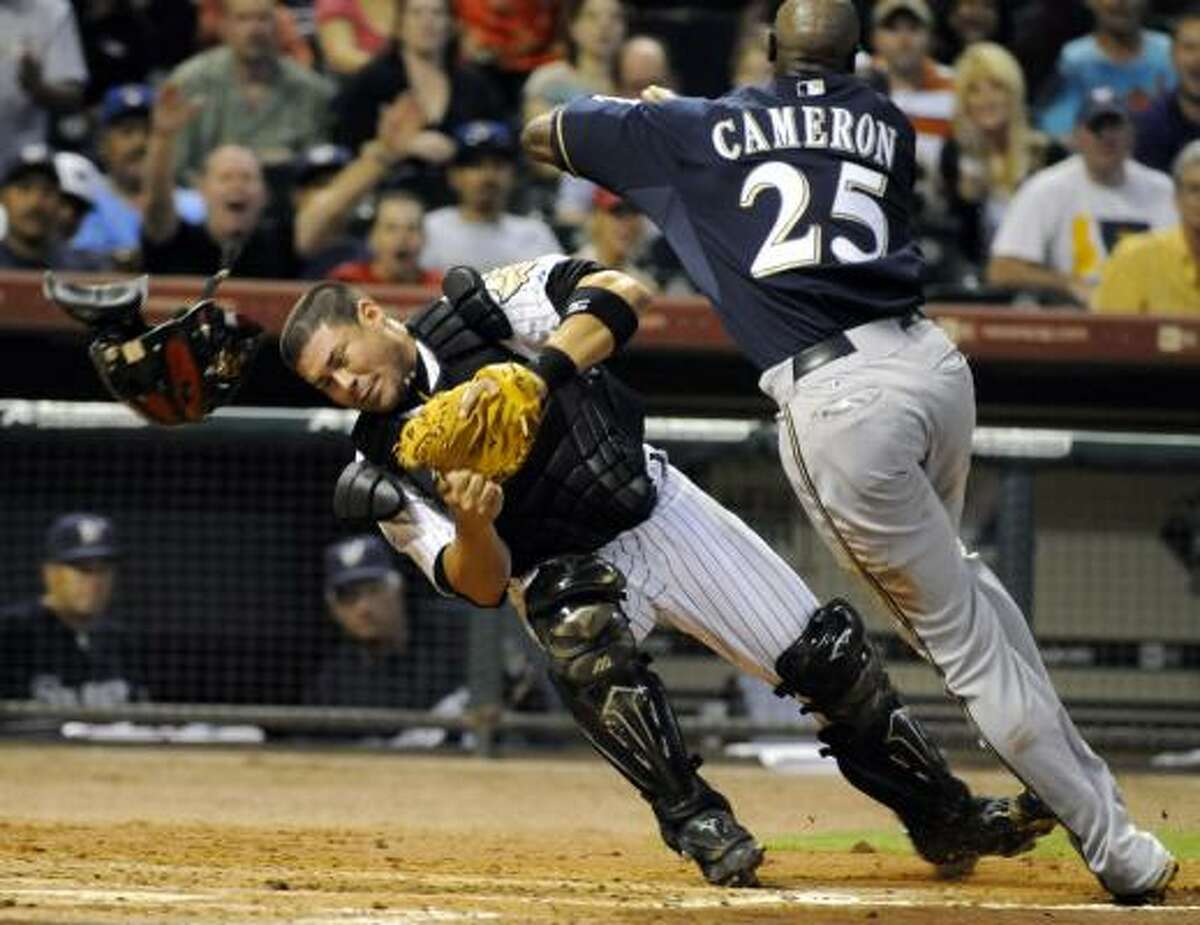 The helmet of Astros catcher Humberto Quintero gets knocked off during a collision with Milwaukee Brewers center fielder Mike Cameron.