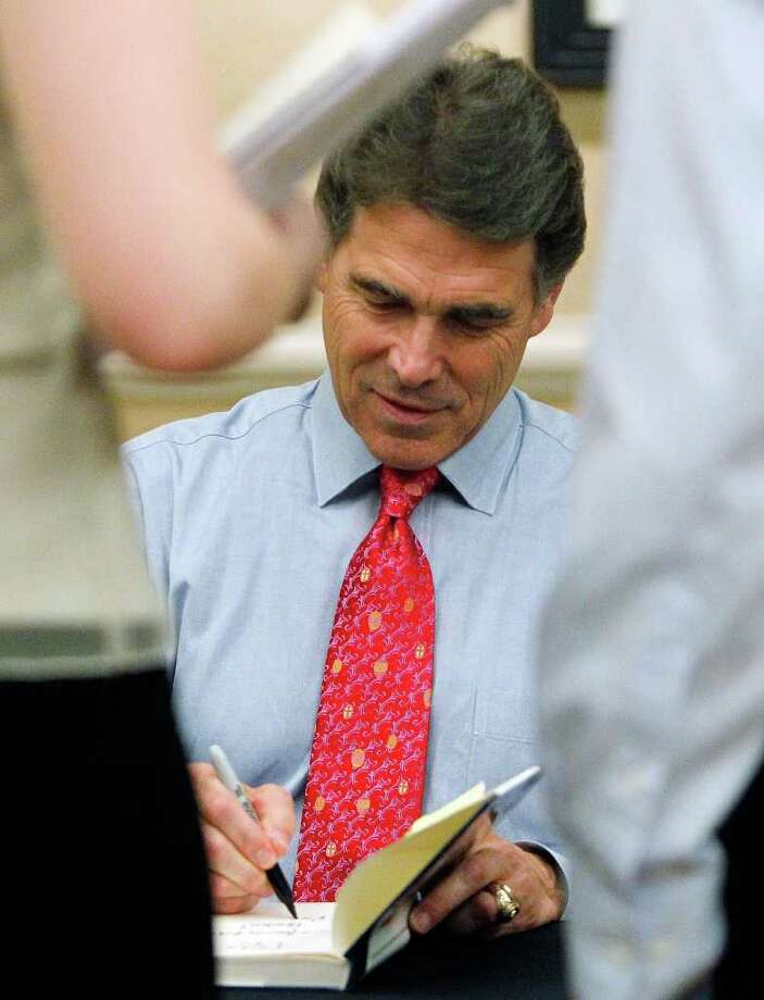 "Texas Governor Rick Perry autographs his book ""Fed Up"" prior to speaking at the Western Conservative Summit in Denver on Friday, July 29, 2011. Perry and former Pennsylvania Sen. Rick Santorum are scheduled to give keynote addresses Friday night. (AP Photo/Ed Andrieski) Photo: Ed Andrieski, STF / AP"