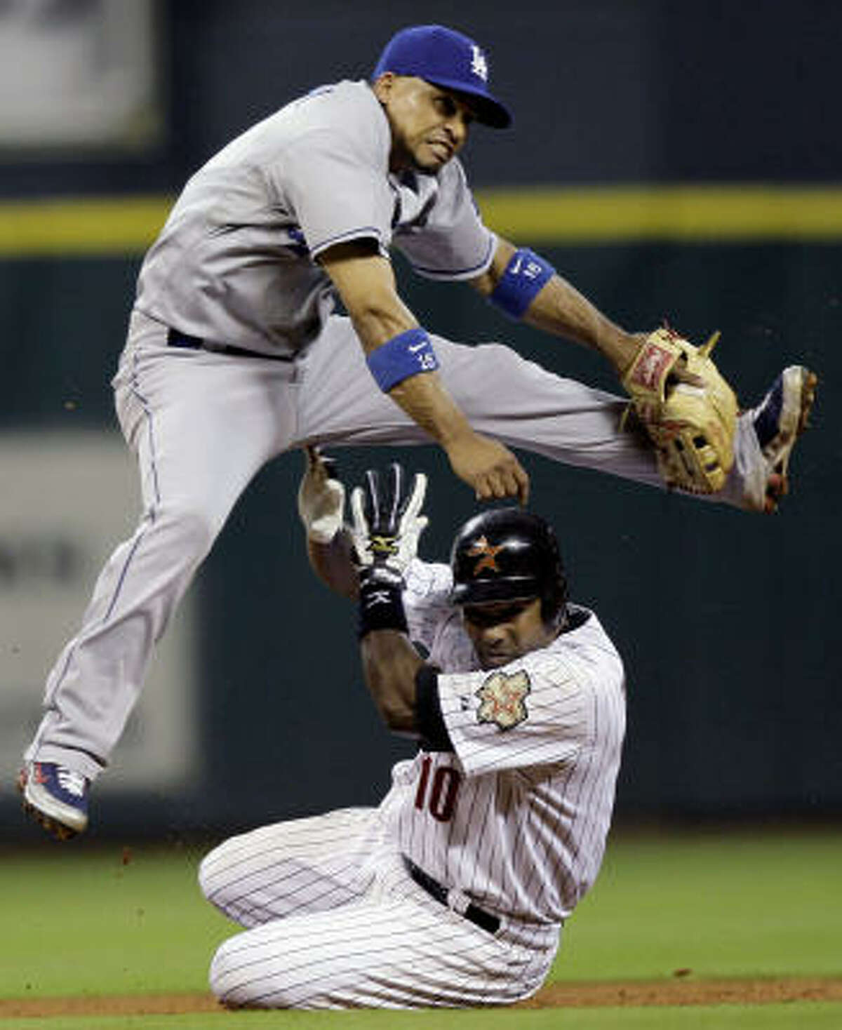 Los Angeles Dodgers shortstop Rafael Furca leaps over Houston's Miguel Tejada while throwing to first base to complete a double play to end the sixth inning of Thursday's game at Minute Maid Park. The Astros lost, 2-0.