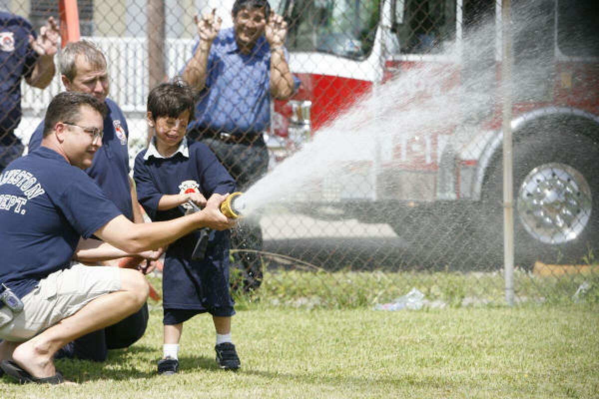 Fahim sprays a fire hose with Galveston Fire Department Captain Paul Chide and Galveston firefighter Jay Jacob, left, while his caregiver Ibraham Mojaddedim, right, watches.