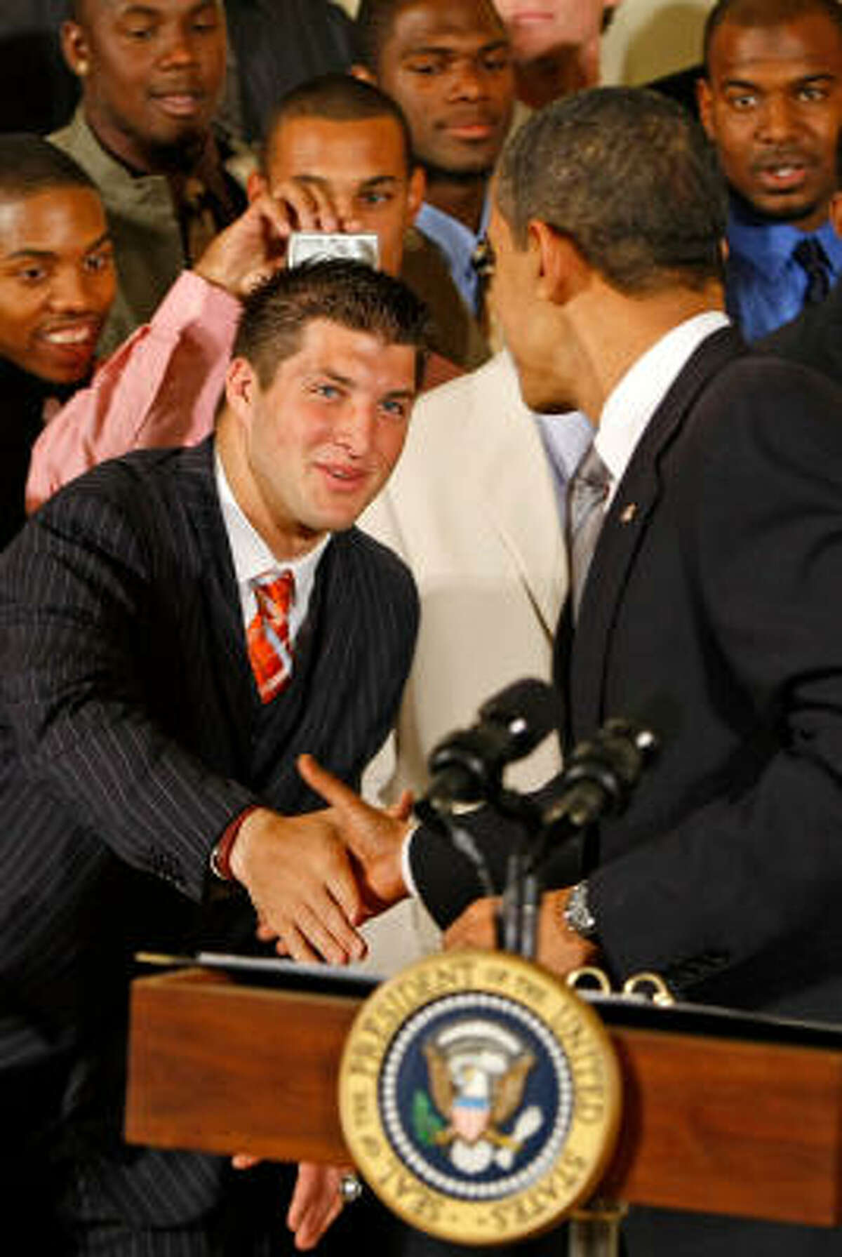 President Obama shakes hands with Florida's star quarterback, Tim Tebow.