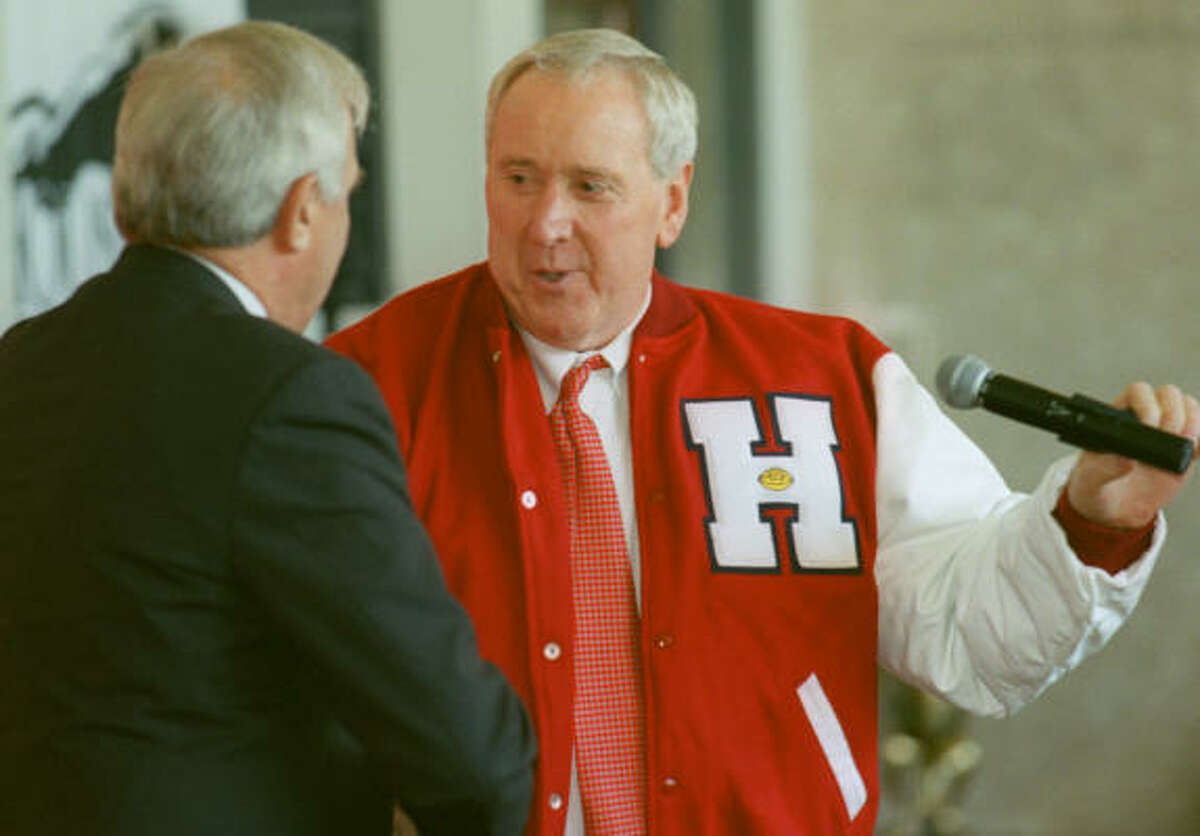 Maggard introduced as athletic director University of Houston President Arthur K. Smith, left, shakes hand with new AD Dave Maggard after giving him a letter jacket during his introductory news conference on Jan.8, 2002.
