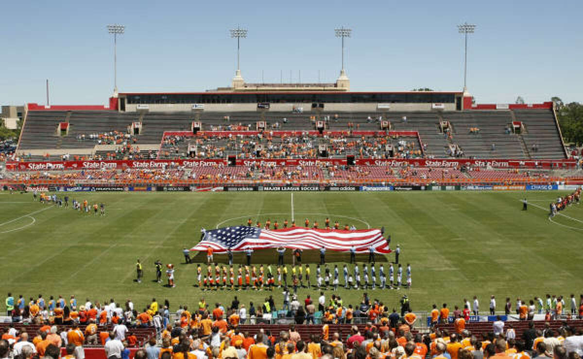 Houston Fire Department officials are seen as they hold on to a large U.S. flag as the Houston Dynamo paused for a moment of silence to remember HFD Captain James Harlow and Fire Fighter Damion Hobs, both from HFD Station 26 who died a week when answering to a fire, before the start of a game between the Houston Dynamo and the Colorado Rapids at Robertson Stadium on Sunday, April 19, 2009, in Houston. ( Julio Cortez / Chronicle )