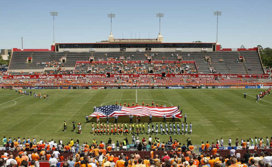 Houston Fire Department officials are seen as they hold on to a large U.S. flag as the Houston Dynamo paused for a moment of silence to remember HFD Captain James Harlow and Fire Fighter Damion Hobs, both from HFD Station 26 who died a week when answering to a fire, before the start of a game between the Houston Dynamo and the Colorado Rapids at Robertson Stadium on Sunday, April 19, 2009, in Houston. ( Julio Cortez / Chronicle ) Photo: Julio Cortez, Houston Chronicle