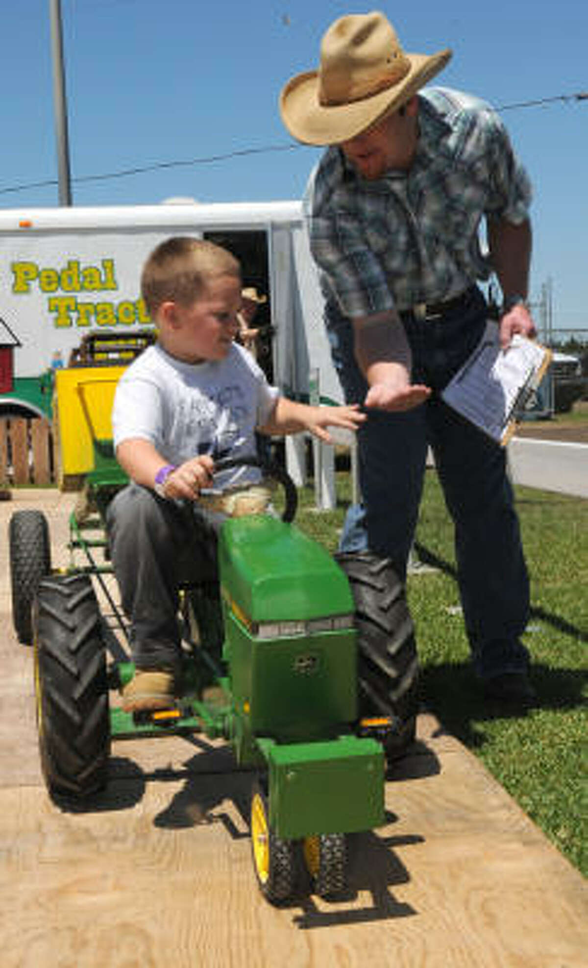 Jeremy Welch, 6, greets Ky Dobbson after crossing the finish line in the pedal-tractor pull competition at the Galveston County Fair and Rodeo in Hitchcock. The event opened Friday and runs through April 25.