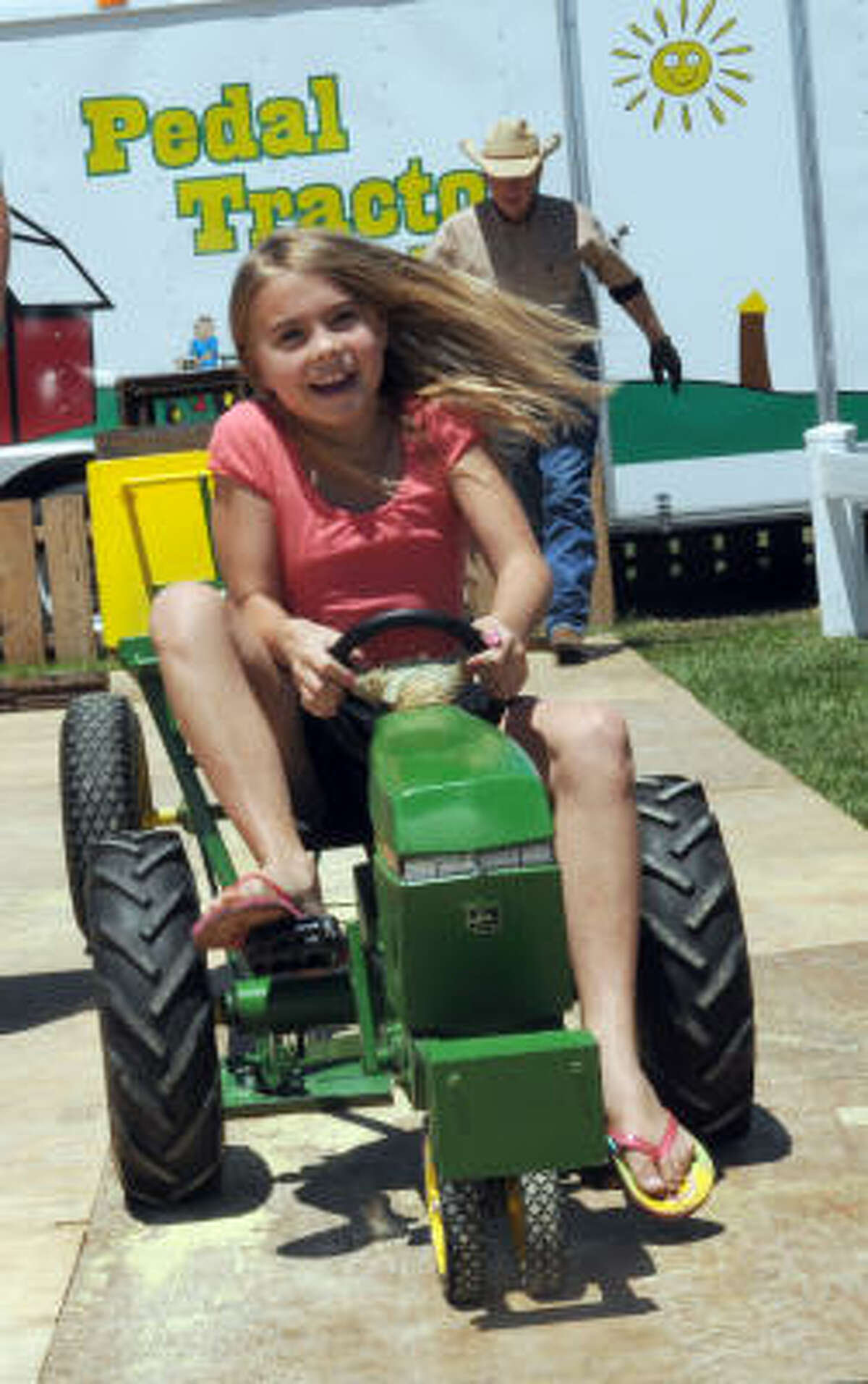 Shelby Walker, 7 works hard to pull her load in the pedal-tractor pull competition at the fair, which is at Jack Brooks Park. The fair dates to 1938.