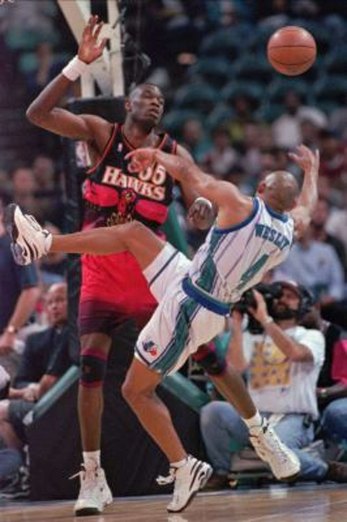 Dikembe Mutombo, then with Atlanta, fouls Charlotte's David Wesley in a 1998 playoff game. The center was named top NBA defender that season and in 1994-95, 1996-97 and 2000-01.
